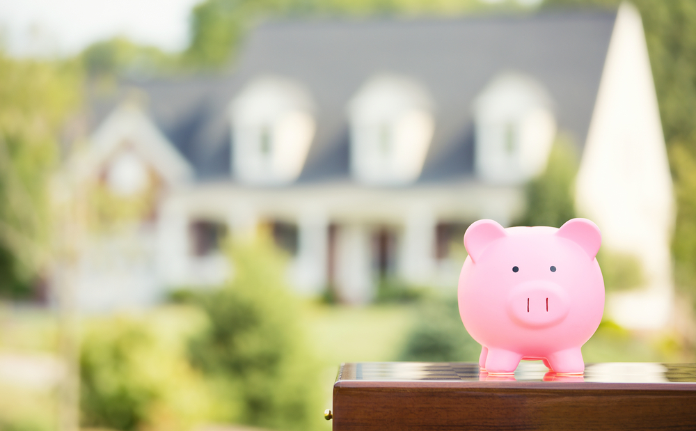 Real estate sale, home savings, loans market concept. Housing industry mortgage plan and residential tax saving strategy. Piggy bank isolated outside home on background. Focus on piggybank. Homeowner (1)